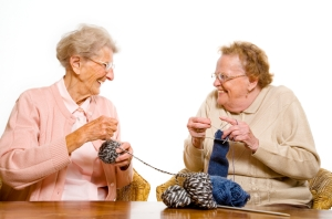 Two senior women laughing, knitting