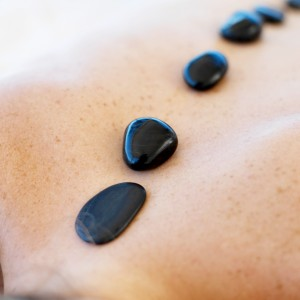 Young Woman with Heated Stones Lined Along Spine
